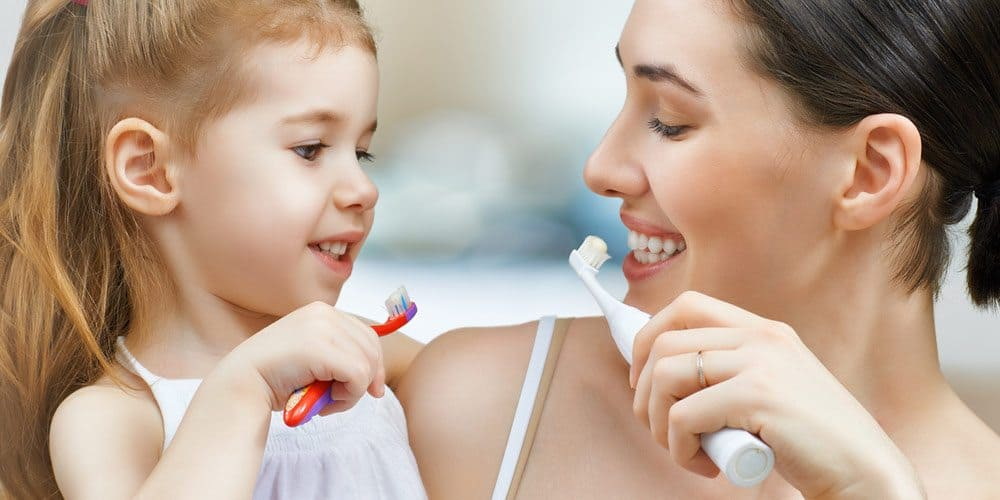 child behavior - Child and mother brushing teeth together smiling